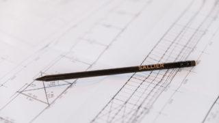 Sallier Bauträger Bauplan mit Bleistift im Büro