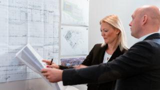 Sallier Bauträger zwei Mitarbeiter am Bauplan Projektentwicklung Handelsimmobilie